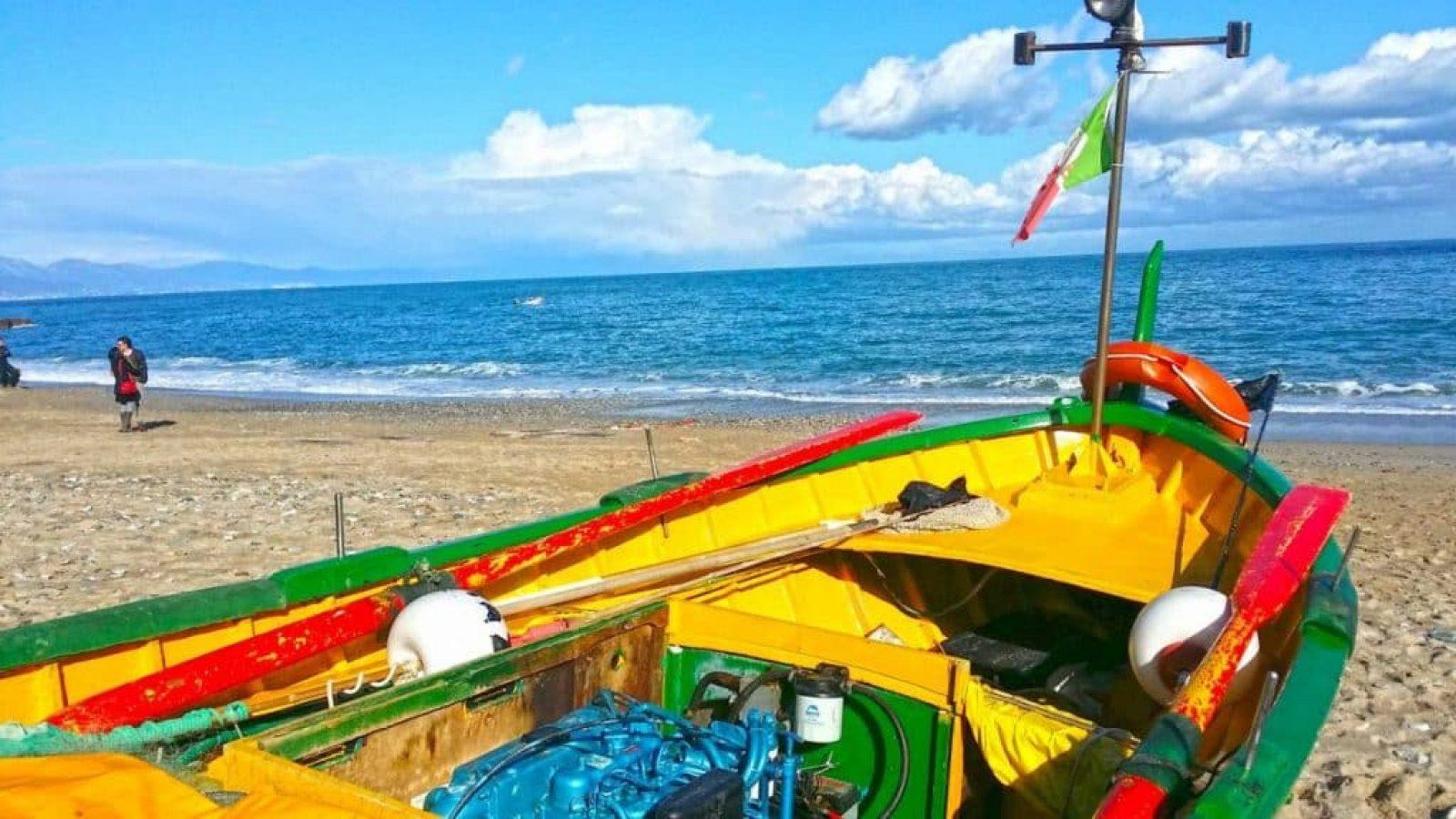 Ein buntes Fischerboot liegt am Strand. Die Wellen des Mittelmeeres gleiten über den Kiesstrand. Feriendomizile in Ligurien mieten